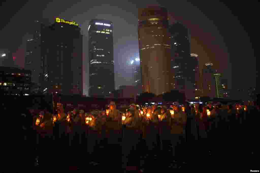 People hold candles during an event attempting to establish a Guinness world record for 'blowing out the most number of candles simultaneously' during Earth Hour in Shanghai.
