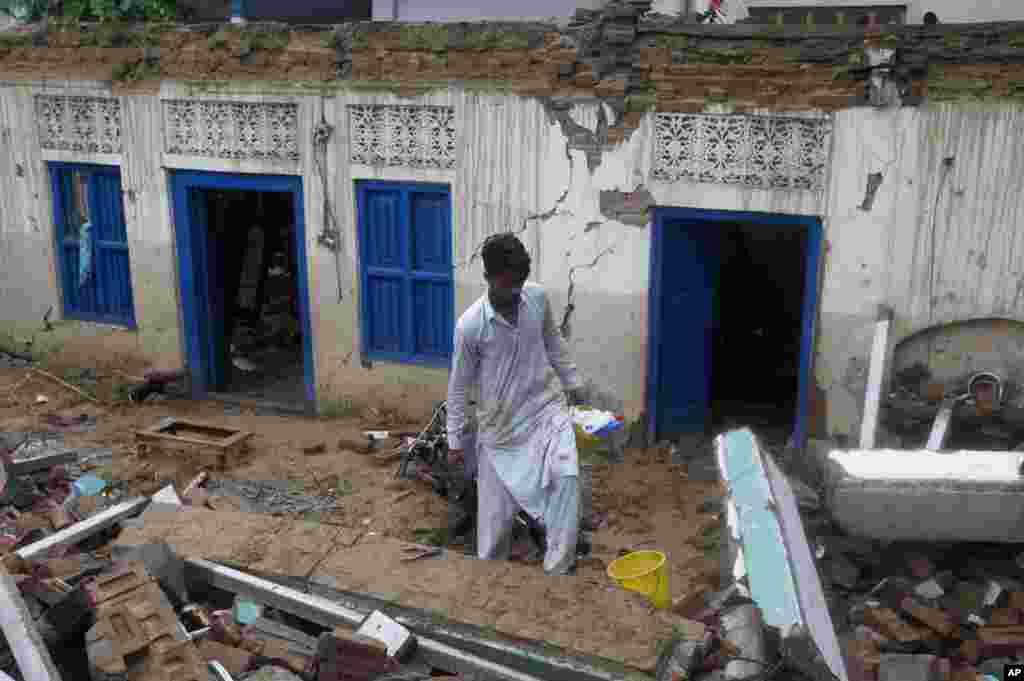 میرپور کے قریب واقع ساہانگ ککری گاوں میں ایک شخص زلزلے سے تباہ ہوجانے والے مکان کے ملبے سے کارآمد چیزیں تلاش کررہا ہے