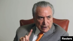 FILE - Brazil's President Michel Temer, gestures during an interview with Reuters at his office in Brasilia, Brazil, Jan. 16, 2017.