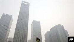 A woman walks past high rise buildings shrouded with hazy skyline in Beijing, China, 09 Oct 2010