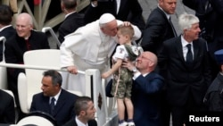 Pope Francis kisses a child at the end of a mass in Saint Peter's Square at the Vatican, May 19, 2013.