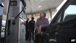 هاوڵاتیـیهکی ئێرانی له بهنزینخانهیهکی تاران بهنزین دهکاته ئۆتۆمبیلهکهی، یهکشهممه 19 ی دوازدهی 2010