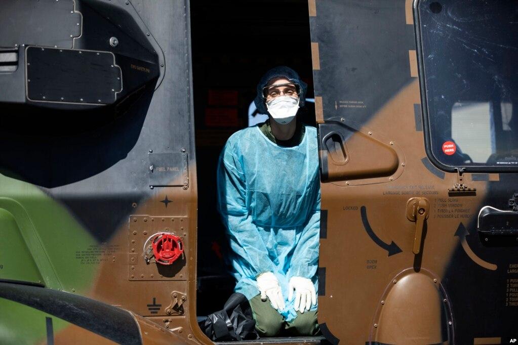 Un profesional médico se arrodilla en un helicóptero militar francés antes de evacuar a Suiza a un paciente infectado con el virus COVID-19, en Estrasburgo, al este de Francia.