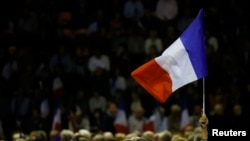 FILE - A supporter raises a French flag at a campaign rally in Nimes, France, Nov. 18, 2016.