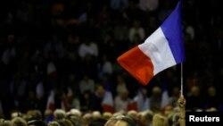 ຜູ້ສະໜັບສະໜູນຄົນໜຶ່ງ ຍົກທຸ' ຝຣັ່ງ ຂຶ້ນ ໃນເວລາທີ່ທ່ານ Nicolas Sarkozy, ອະດີດຫົວໜ້າພັກ Les Republicains ແລະ ຜູ້ລົງແຂ່ງຂັນການເລືອກຕັ້ງຂັ້ນ ຕົ້ນເອົາຕຳແໜ່ງປະທາ ນາທິບໍດີ ສຳລັບພັກການເມືອງນິຍົມກາງຂວາຂອງ ຝຣັ່ງ ເຂົ້າ ຮ່ວມໃນການຊຸມນຸມໂຄສະນາຫາສຽງໃນເມືອງ Nimes, ປະເທດ ຝຣັ່ງ, 18 ພະຈິກ, 2016.