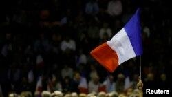 """Seorang pendukung mengibarkan bendera Perancis ketika Nicolas Sarkozy, mantan pemimpin partai politik """"Les Republicains"""" dan kandidat pemilihan pendahuluan presiden Perancis menghadiri kampanye di Nimes, Perancis, 18 November 2016."""