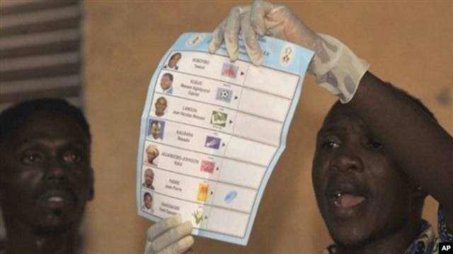 A Togolese electoral holds up a ballot papers in a polling station in Lome, 04 Mar 2010