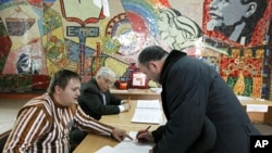 An election official assists a man with his ballot papers at a polling station in the Southern Russian city of Stavropol, March 13, 2011