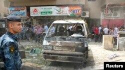 伊拉克保安人员检查巴格达的一个爆炸现场