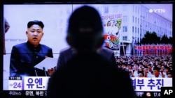 Un hombre mira un programa de televisión que muestra la foto de Kim Jong-un, el líder norcoreano que sigue sin aparecer en público.
