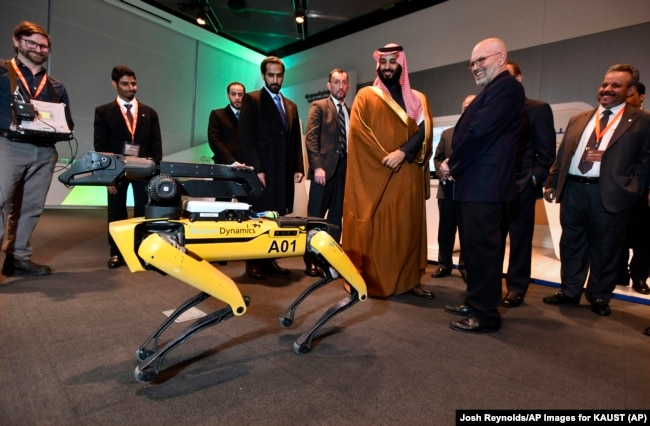 "Saudi Crown Prince Mohammed bin Salman visits a demonstration of technology, including a robotic ""SpotMini"" dog presented by Boston Dynamics CEO Marc Raibert, during a visit to Massachusetts Institute of Technology on Saturday, March 24, 2018."
