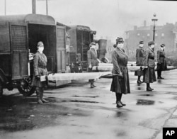 In this photo made available by the Library of Congress, St. Louis Red Cross Motor Corps personnel wear masks as they hold stretchers next to ambulances in preparation for victims of the influenza epidemic.