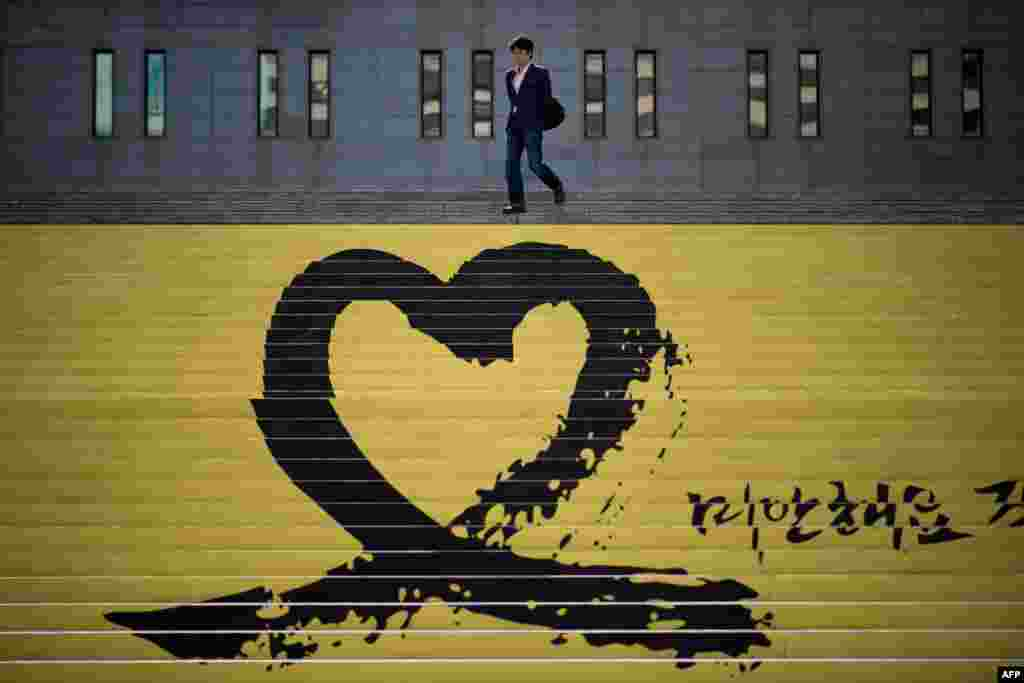 A man walks down steps past a tribute to victims of the Sewol ferry, in Seoul, South Korea. The confirmed death toll stands at 273, with 31 still unaccounted for, after four more bodies were retrieved from the sunken ship overnight.