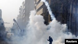 A protester throws a tear gas canister back at riot police in Cairo, November 25, 2012.