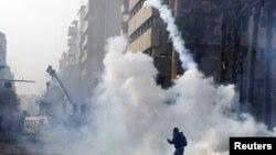 11月25日开罗一名抗议者把催泪瓦斯罐扔回防暴警察