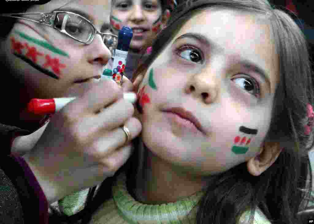 2013年3月20日在叙利亚阿勒颇举行的一个节庆中,女孩在脸上画上叙利亚革命旗帜的颜色。