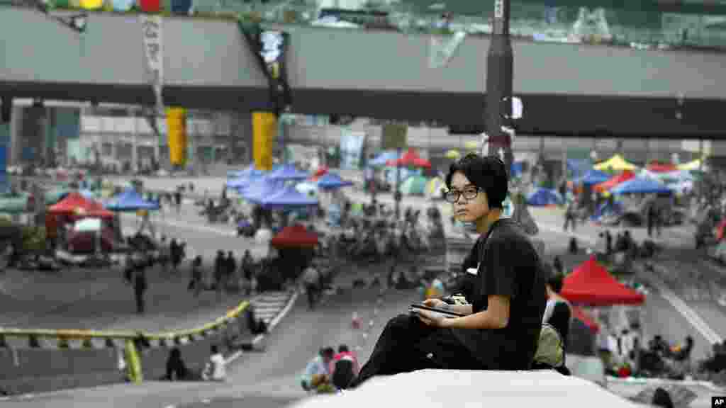 A pro-democracy student protester wakes after a night on the occupied roads of the financial district Hong Kong, Sunday, Oct. 5, 2014.