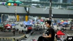 Seorang siswa pro-demokrasi menginap di jalan tempat demo berlangsung di Hong Kong, Minggu, 5 Oktober 2014.