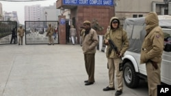 Indian police officers stand outside the district court where five men accused in a gang rape were brought to appear in New Delhi, January 7, 2013.