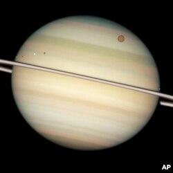 ناسا کی خلائی دور بین سے اتارئی گئی زحل کی تصویر جس میں اس کے گرد گھومنے والے کئی چاند بھی دکھائی دے رہے ہیں۔ بڑا چاند ٹائی ٹین نمایاں ہے۔