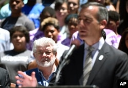 Filmmaker George Lucas, left, listens to remarks by Los Angeles Mayor Eric Garcetti at a news conference outside Los Angeles City Hall, June 27, 2017.