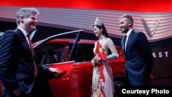 Cựu danh thủ bóng đá Anh David Beckham (phải), hoa hậu Việt Nam 2018 Trần Tiểu Vy (giữa) và giám đốc thiết kế của VinFast Dave Lyon giới thiệu chiếc xe ô tô đầu tiên của Việt Nam tại buổi lễ ra mắt ở Paris Motor Show hôm 1/10.