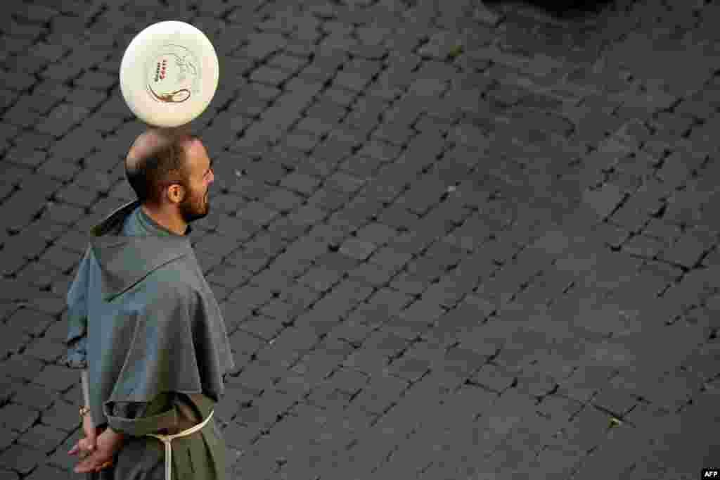 Seorang biarawan bermainFrisbee diPiazza Santi Apostoli diRoma.