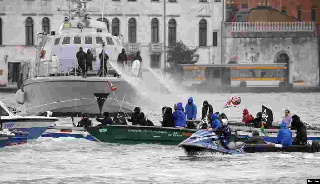 Guardia di Finanza police spray water cannons at NO TAV (no high speed train) protesters in the Venice lagoon, before the meeting between Italian Prime Minister Matteo Renzi and French President Francois Hollande during the annual Franco-Italian summit in Venice, Italy.