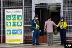Petugas keamanan memeriksa akreditasi dan suhu tubuh seorang pria yang memasuki Tokyo Big Sight, situs International Broadcast Center (IBC) dan Main Press Center (MPC) Tokyo 2020, 9 Juli 2021. (Foto: AFP)