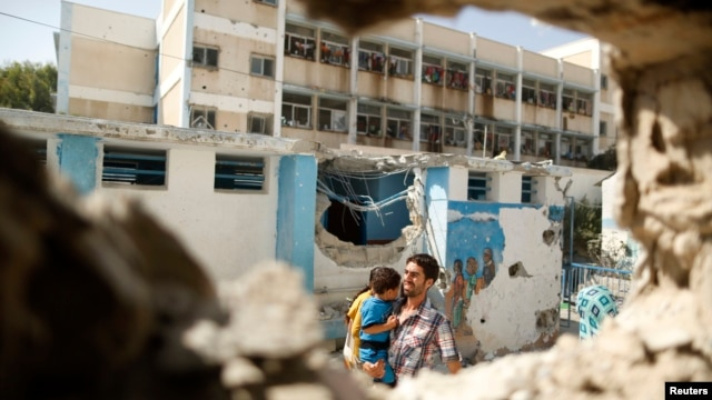 Palestinian man carries boy past UN-run school that was struck whole sheltering those displaced by Israeli ground offensive, Jebalya northern Gaza, July 30, 2014.