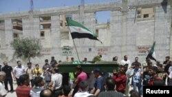 Demonstran anti pemerintah membawa jenzah Yaser Raqieh yang menurut mereka dibunuh oleh pasukan keamanan Suriah di dekat Hama (5/6).
