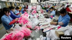 In this 2013 file photo, employees work on an assembly line at a shoe factory in Tan Lap village, outside Hanoi. Vietnam adopted a broad plan to boost its economy.