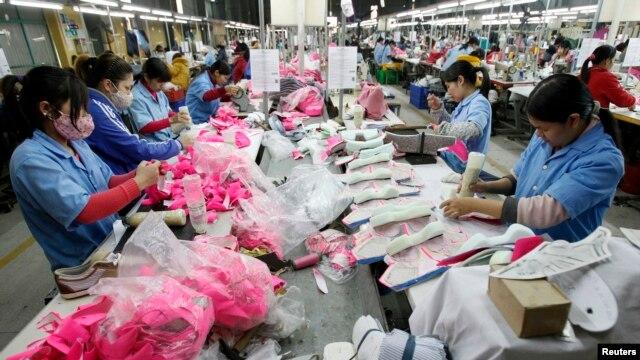 Công nhân làm việc trên một dây chuyền lắp ráp tại nhà máy giày ở xã Tân Lập, ngoại ô Hà Nội.