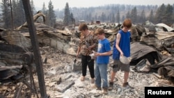 From left, Mim Morris looks through the remnants of her home, which was destroyed by the Carlton Complex Fire, as her grandsons Sean Lafer, 12, and Joel Lafer, 14, join her near Malott, Washington, July 20, 2014.