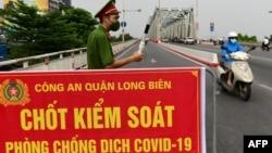 Một công an đứng canh tại một chốt kiểm soát ở Hà Nội ngày 29/7/2021. Bộ Y tế Việt Nam vừa quyết định giảm thời gian cách ly tập trung cho người nhập cảnh đã tiêm vaccine đầy đủ xuống còn 7 ngày.