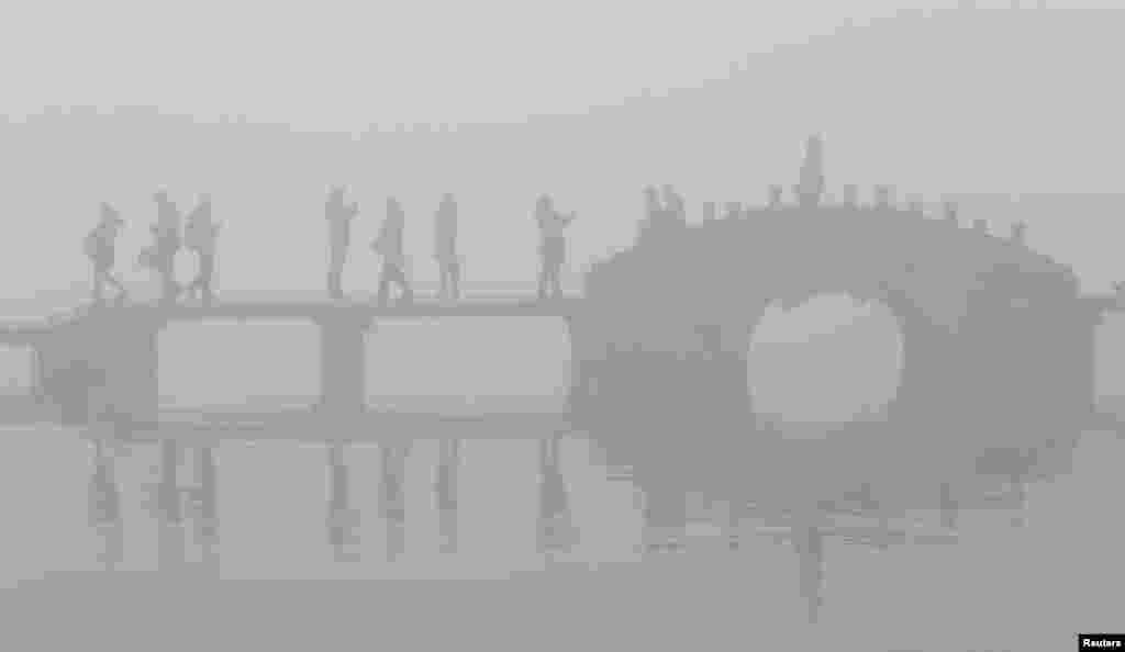 អ្នកទេសចរដើរលើស្ពានមួយ នៅពេលពួកគេទៅទស្សនាបឹង West Lake ចំពេលមានអ័ព្ទក្រាស់ និងផ្សែងយ៉ាងច្រើននៅក្នុងក្រុង Hangzhou ខេត្ត Zhejiang ប្រទេសចិន។