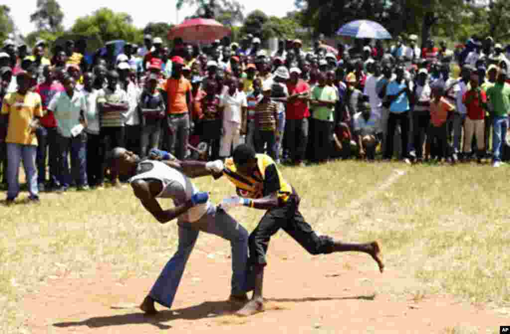Fist fighters battle during the Musangwe, an age old tradition where men and boys display their fighting skills, at Gaba Village in Limpopo province December 22, 2011. The annual Venda fist-fighting run by community leaders, attracts hundreds of men who e
