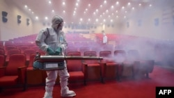 South Korean health officials fumigate a theater while wearing protective gear in Seoul, June 12, 2015.