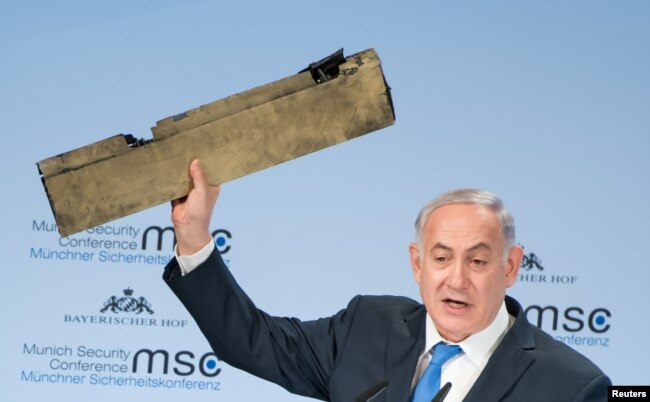 Israeli Prime Minister Benjamin Netanyahu holds up a remnant of what he said was a piece of Iranian drone which was shot down in Israeli airspace during his speech at the Munich Security Conference, Germany, Feb. 18, 2018.