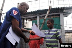 FILE - Moses Duo, 9, receives a certificate for being cured of the Ebola virus in Paynesville, Liberia, July 20, 2015.