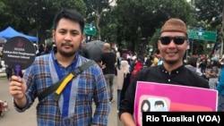 Christian Patricho Adoe dari Gerakan Mahasiswa Kristen Indonesia (GMKI) dan Andre Flo dari Gusdurian Jakarta mengikuti pawai untuk mendesak pengesahan RUU Penghapusan Kekerasan Seksual (P-KS), Jakarta, Sabtu, 8 Desember 2018. (Foto: Rio Tuasikal/VOA)