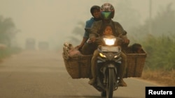 A family rides on a motorcycle as the haze from fires hits Kubu district in Rokan Hilir, in Indonesia's Riau province, June 25, 2013.