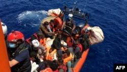 51 migrants, qui dérivaient sur un bateau en bois, sont secourus par des membres de l'ONG française SOS Mediterranée, au large des côtes de l'île de Lampedusa, le 25 juin 2020.