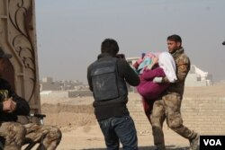 An Iraqi soldier carries a wounded girl into Mosul's only clinic for treatment before transport to a hospital, Nov. 27, 2016. (H. Murdock/VOA)