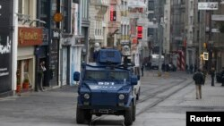FILE - An armored police vehicle drives along an empty Istikal street, following a suicide bombing in a major shopping and tourist district in central Istanbul, March 19, 2016.