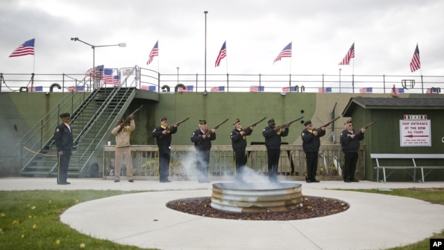 Members of American Legion Post 9, and VFW Post 9388 fire a 21-gun salute during a flag retirement ceremony, Sunday, Nov. 10, 2013, in front of the USS LST 393 Veterans Museum in Muskegon, Michigan.