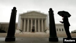 FILE - A man with an umbrella is seen outside the U..S. Supreme Court building in Washington, D.C.