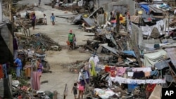 Survivors of Typhoon Haiyan walk amid ruins of their homes in Maraboth, Philippines, Nov. 14, 2013.