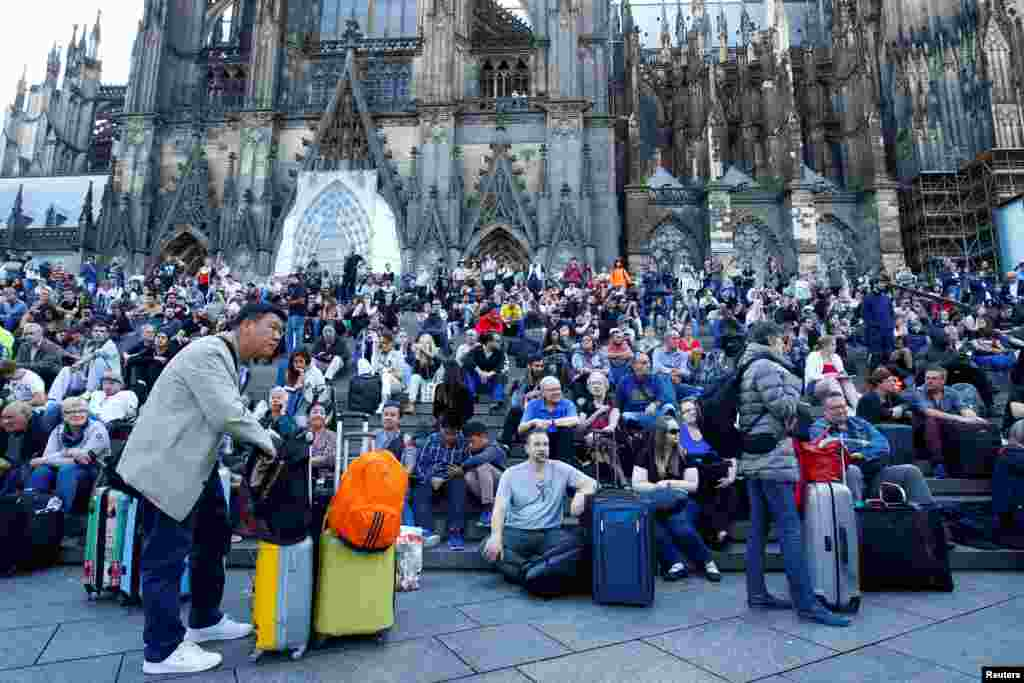 Passengers wait outside the main train station in Cologne, Germany, as the train station was closed due to a suspected hostage-taking.