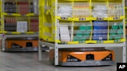 In this Dec. 5, 2018, photo, pods full of merchandise are moved around the floor by robotic drives, named Amazon robots, at the Amazon fulfillment center on Staten Island borough of New York. (AP Photo/Mary Altaffer)
